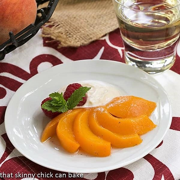 Poached peach fanned out on a white dessert plate