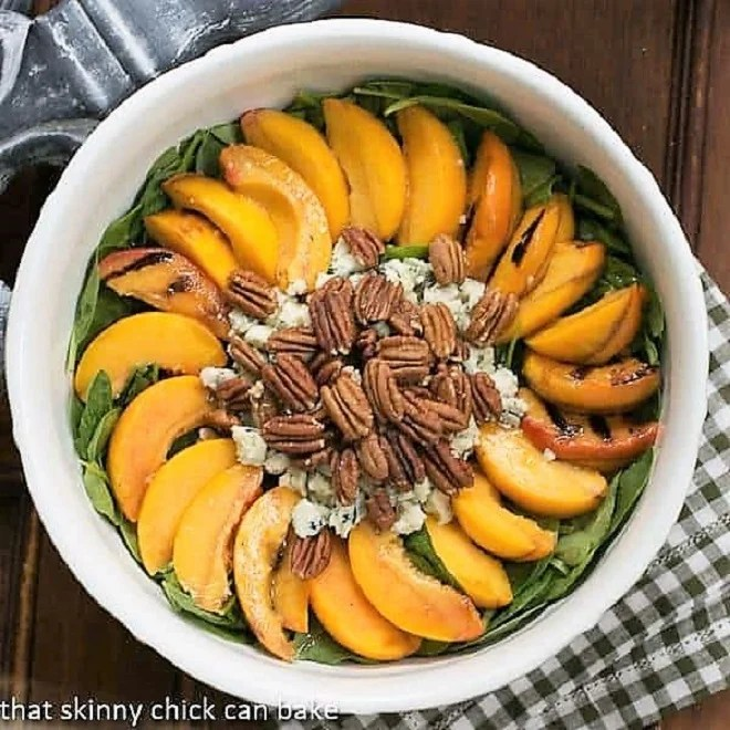 Overhead view of a bowl of Spinach Salad with Grilled Peaches and Blue Cheese