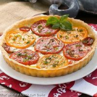 Summer tomato tart on a white plate garnished with a sprig of fresh basil