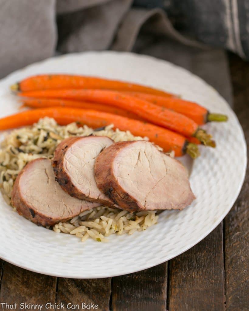 Whiskey Marinated Pork Tenderloin, grilled and sliced on a white dinner plate