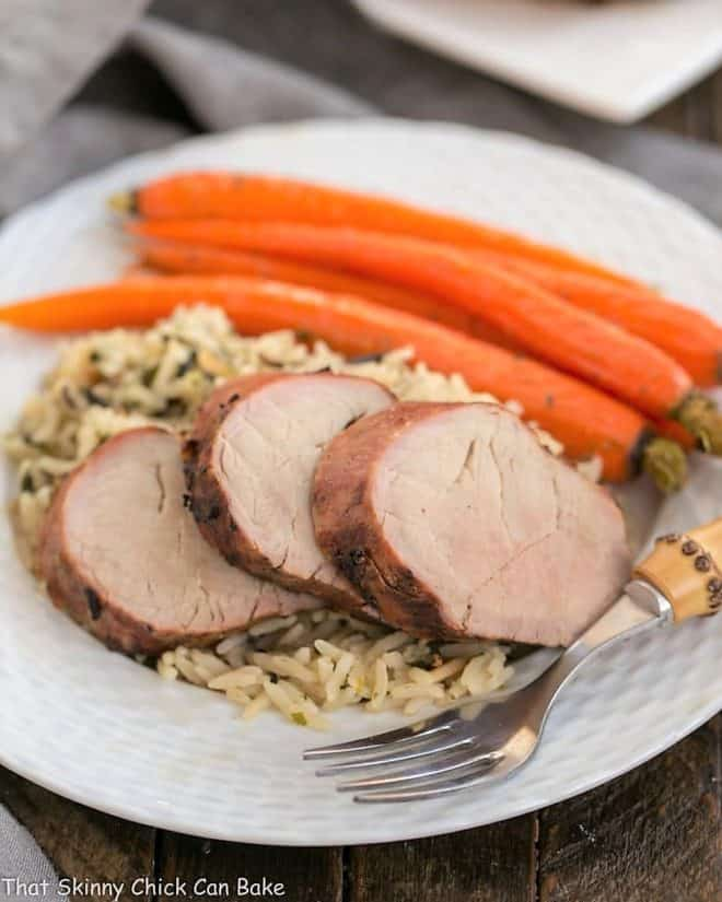 Whiskey Marinated Pork Tenderloin with rice and carrots on a white plate