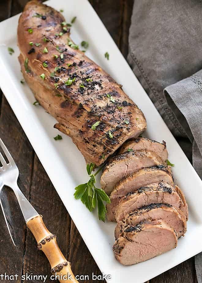 Grilled pork tenderloin on a rectangular white platter