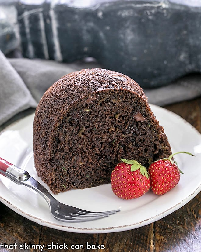 Slice of Chocolate Zucchini Bundt Cake on a white plate with a red handle fork and two strawberries