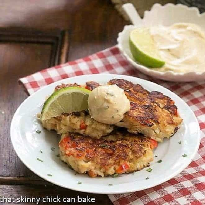 Crab Cakes on a round white plate with lime and aioli