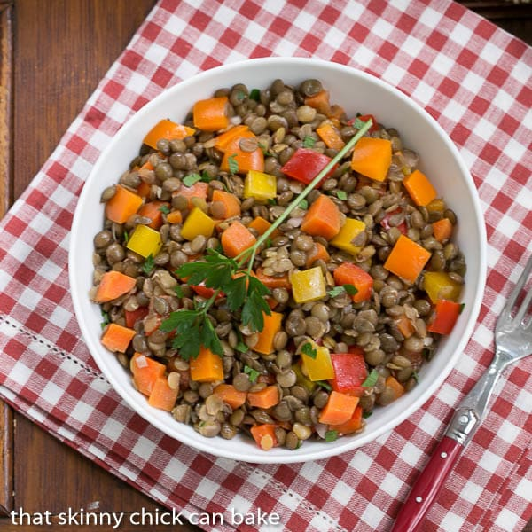 French Lentil Salad in a white bowl on a red and white checked napkin