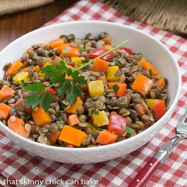 French Lentil Salad in a white serving bowl with a sprig of parsley