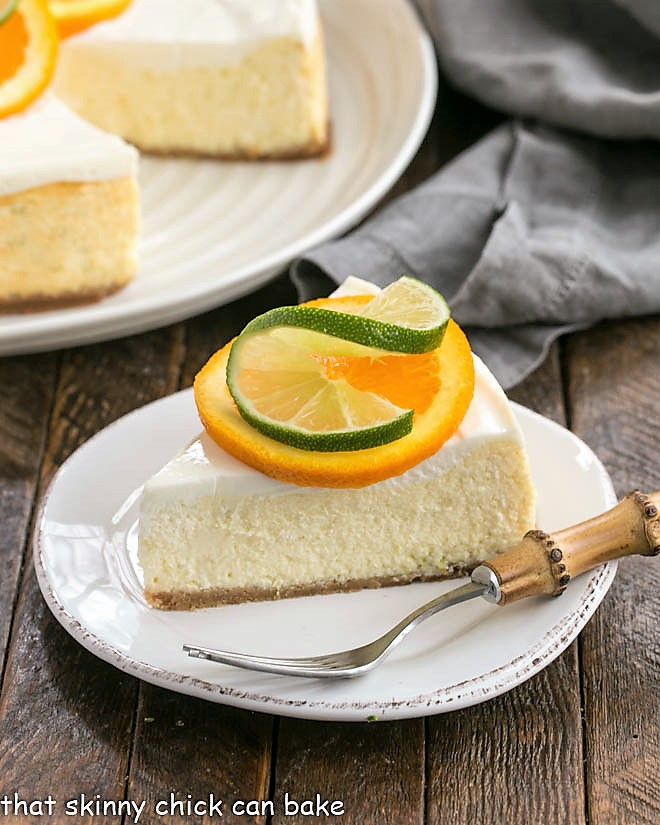 Margarita Cheesecake slice on a white dessert plate garnished with an orange and lime slice