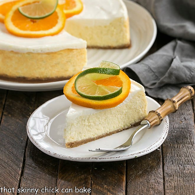 Margarita Cheesecake slice on a white dessert plate garnished with an orange and lime slice in front of the dessert with a slice remove