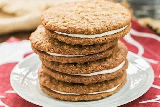A stack of Oatmeal Cream Pies on a white plate over a red and white napkin