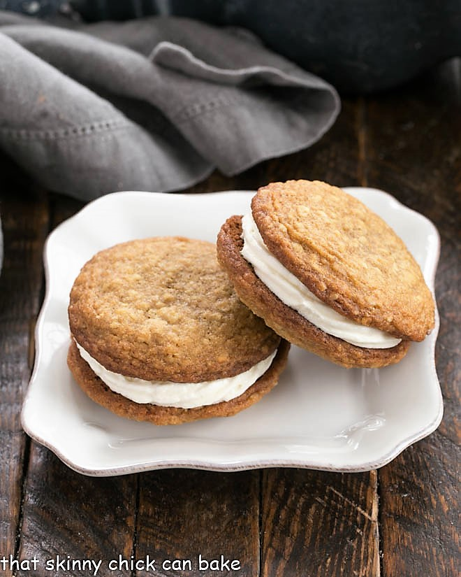 One oatmeal creme pie leaning on another on a square white plate