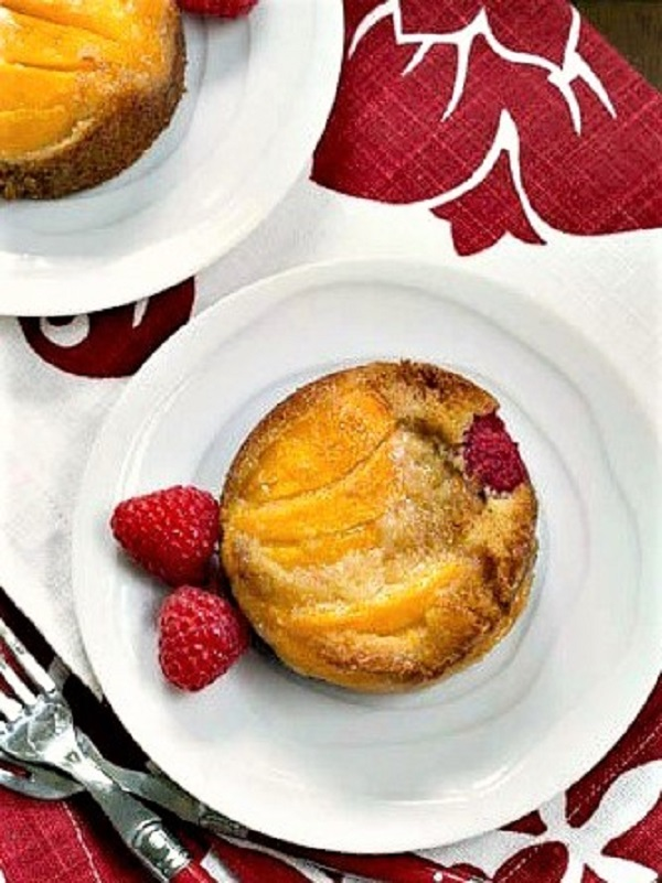 Overhead view of Oven Roasted Peach Cakes on white plates over a red and white napkin