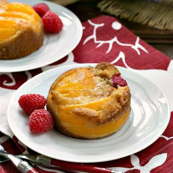 Oven Roasted Peach Cakes on white dessert plates with fresh raspberries