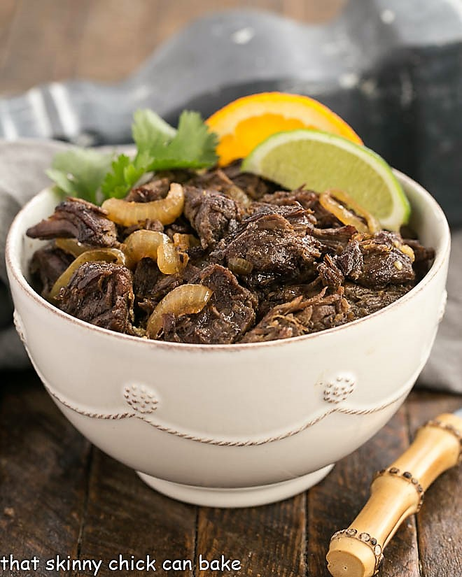 Vaca Frita in a white bowl over rice and garnished with tomatoes and orange and lime slices