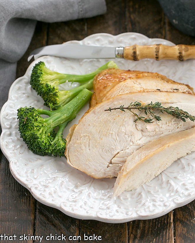 Overhead view of Rotisserie Chicken slices on a white plate with broccoli