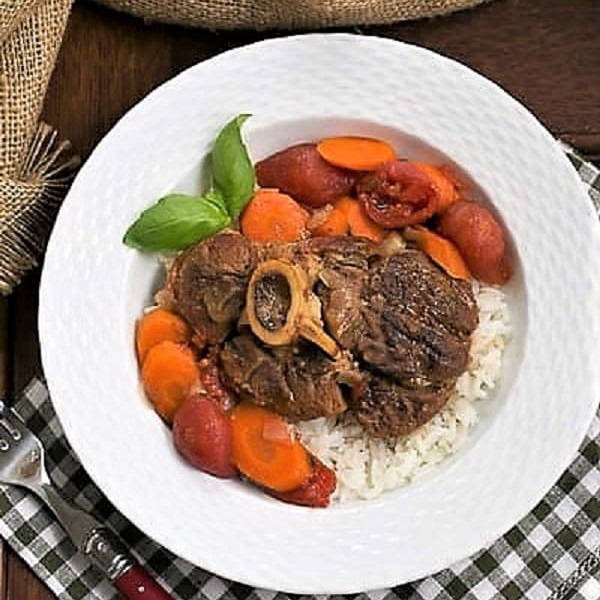 Overhead view of Osso Buco a L'arman in a white bowl over a green and white checked napkin