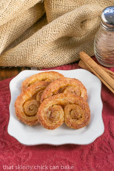 Pumpkin-Palmiers on a square white plate with cinnamon sugar and cinnamon sticks