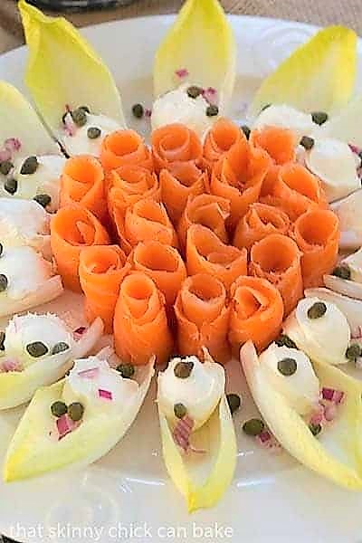 Close view of Smoked Salmon Roses with Endive and Creme Fraiche on a smoked salmon plater