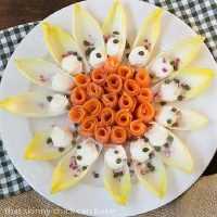 Smoked Salmon Roses with Endive and Creme Fraiche on a round white plate