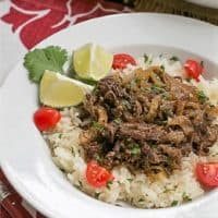 aca Frita or Cuban shredded beef in a white bowl over rice