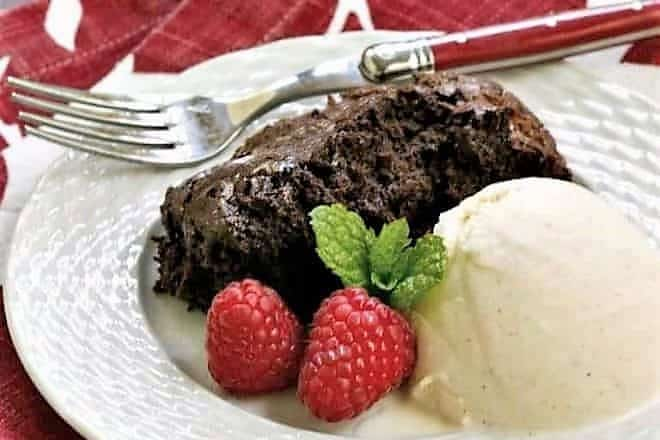 Slow Cooker Brownie Dessert on a white plate with a scoop of ice cream and fresh raspberries