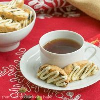 2 cherry pistachio biscotti on a white saucer with a cup of tea
