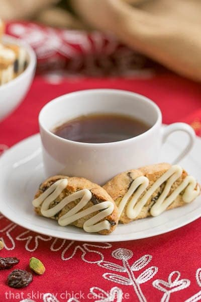 Cherry Pistachio Biscotti on a saucer with a cup of tea