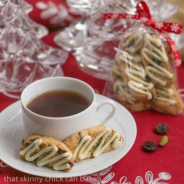 Cherry Pistachio Biscotti sits on a white saucer with a cup of tea. Bags of biscotti are festively wrapped for gifts in the background