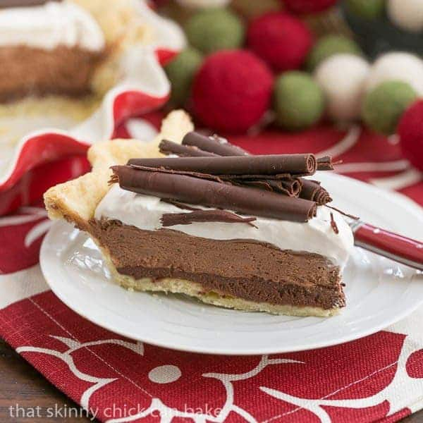 Slice of chocolate mousse pie on a white plate over a red and white napkin