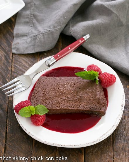 Overhead view of a Slice of Chocolate Terrine with Raspberry Sauce on a white plate with a red handle fork