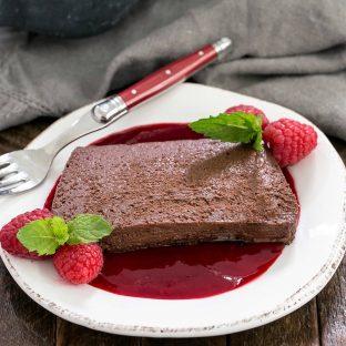 A slice of chocolate terrine over raspberry sauce on a white dessert plate
