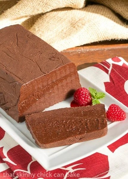 Chocolate Terrine with Raspberry Sauce on a serving tray with one slice and fresh raspberries