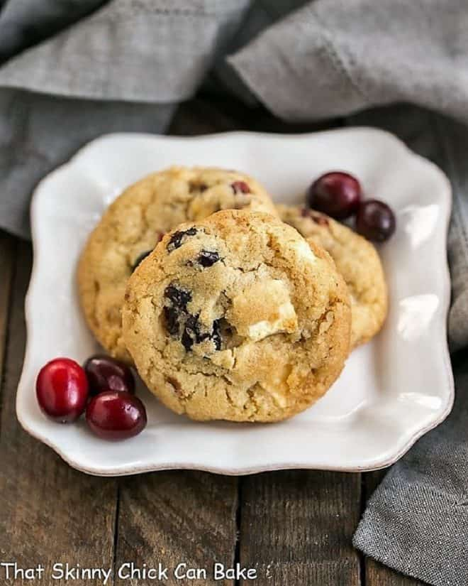Cranberry, White Chocolate, Crystallized Ginger Cookies on a square white plate with fresh cranberries