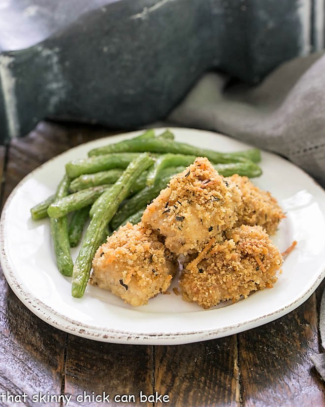 homemade chicken nuggets on a white plate with roasted green beans