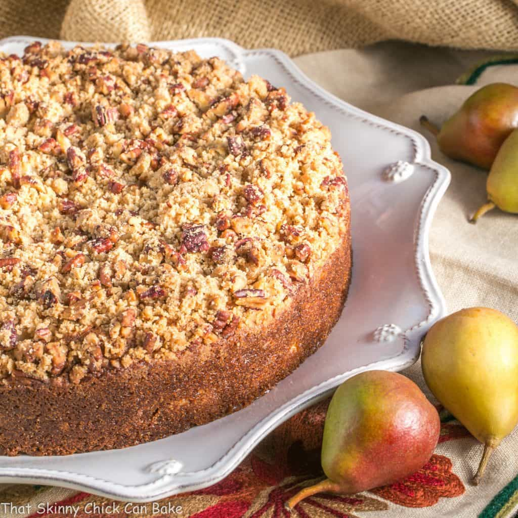 Pear Streusel Coffee Cake on a white platter with fresh pears