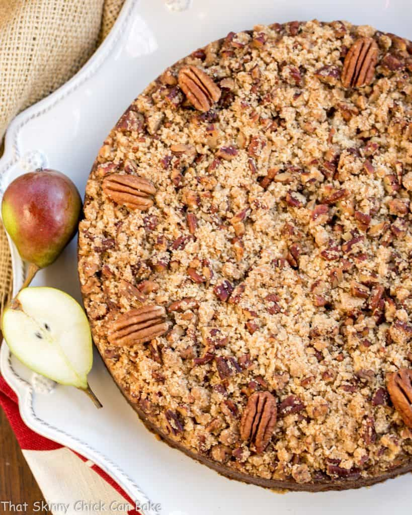 Pear Streusel Coffee Cake viewed from above on a white serving dish with small fresh pears