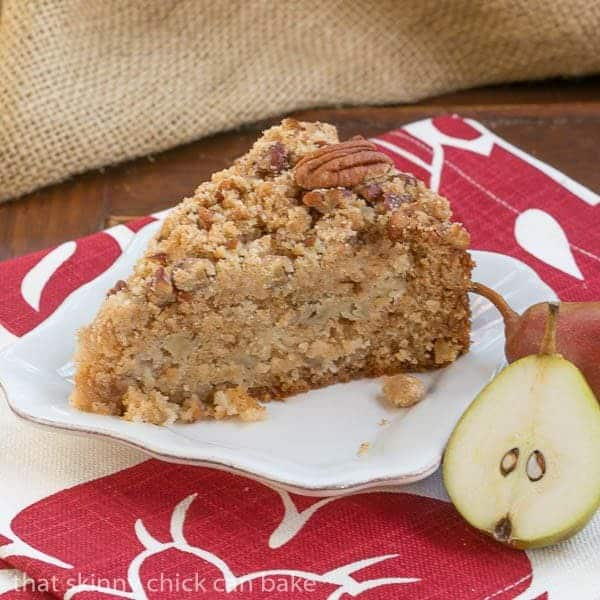 Slice of Pear Streusel Coffee Cake on a square white plate with a pear half