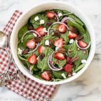 Spinach Strawberry Pomegranate Salad in a serving bowl over a red and white checked napkin