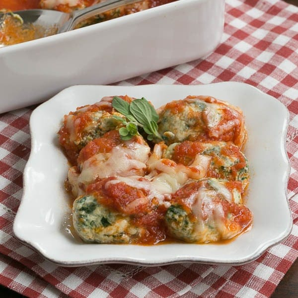 Storzapretis AKA Spinach Gnocchi on a white plate with marinara and cheese