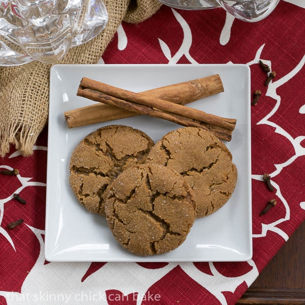 Overhead view of Triple Ginger Snaps with cinnamon sticks on a white plate