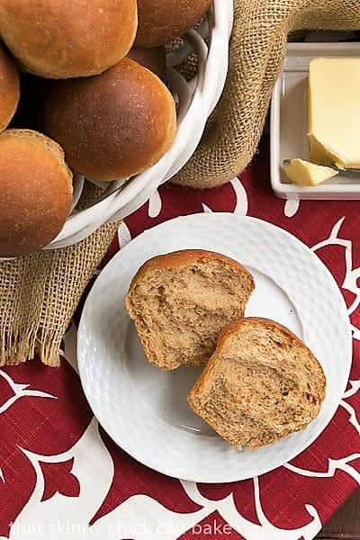 Whole Wheat Dinner Rolls in a basket and one open on a white basketweave plate