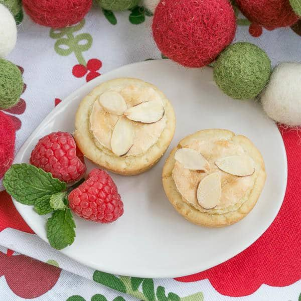 Overhead view of Almond Raspberry Tartlets on an oval white plate