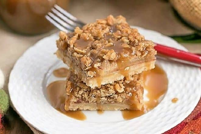 Caramel Apple Streusel Bars stacked on a white plate and drizzled with caramel