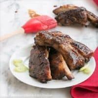 Asian Baby Back Ribs on a white plate with a red basting brush