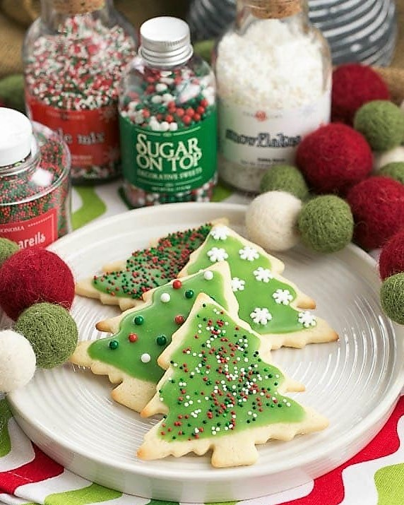 Cut out sugar cookies on a white plate with jars of sprinkles
