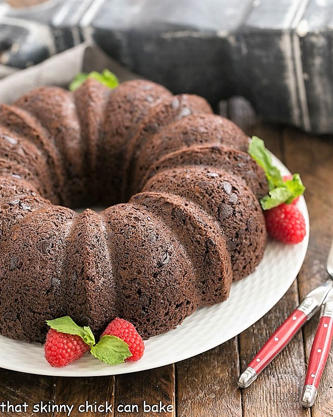 Chocolate Bundt Cake on a white plate garnished with berries and mint