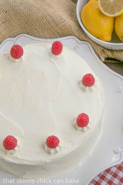 Lemon Mascarpone Layer Cake viewed from above with a bowl of lemons
