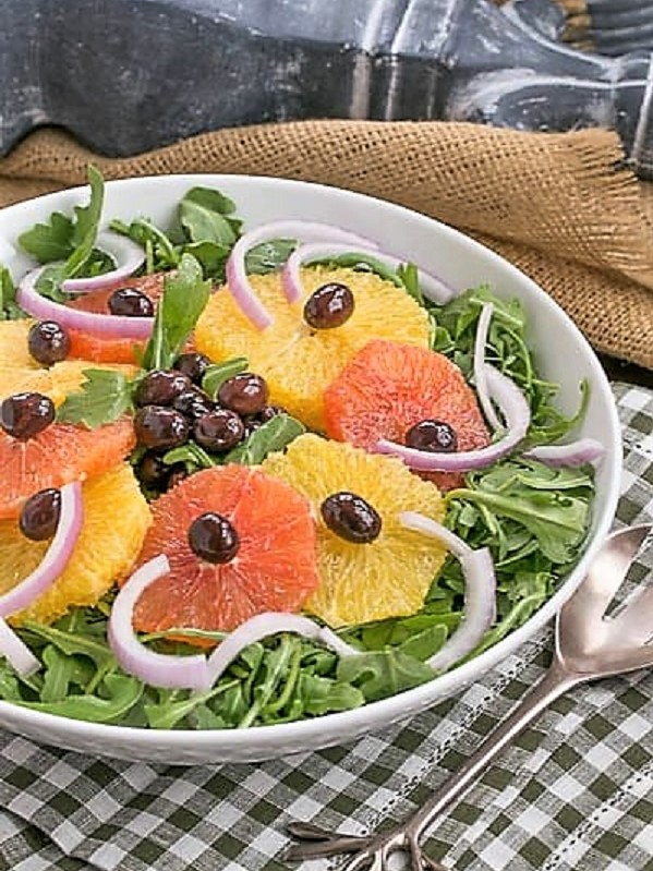 Orange Olive Moroccan Salad on a bed of arugula in a white bowl on a checked napkin