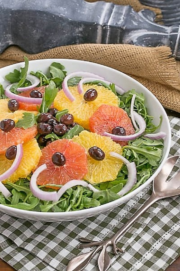 Orange Olive Salad on a bed of arugula in a white bowl on a checked napkin