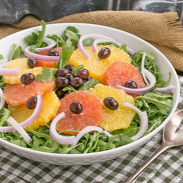 Orange Olive Salad on a bed of arugula in a white bowl