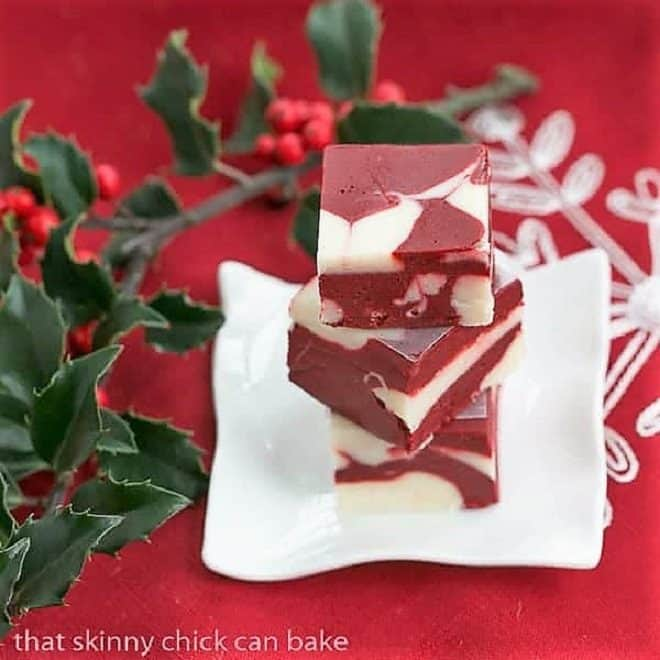 Stack of red velvet fudge on a small white plate with holly berries